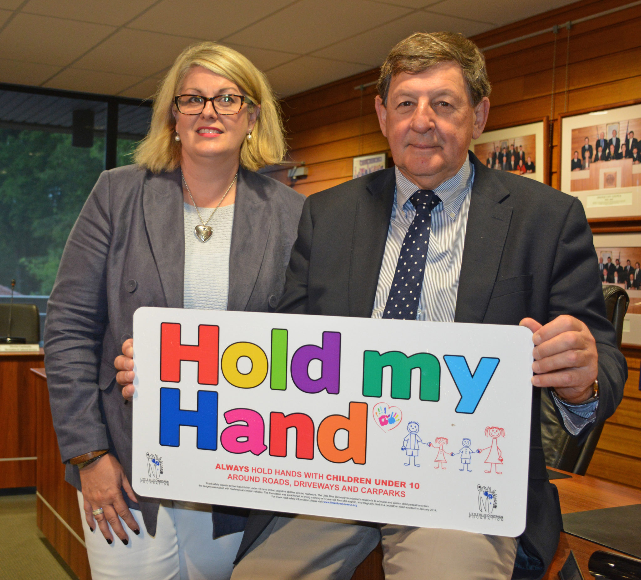 Michelle McLaughlin and Mayor Reg KIdd hold one of the new 'Hold My Hand' road safety signs
