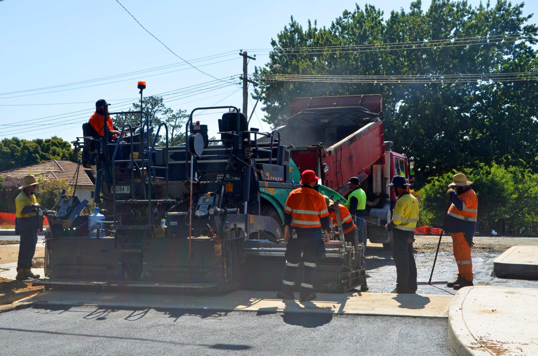 Contractors laying hot-mix asphalt
