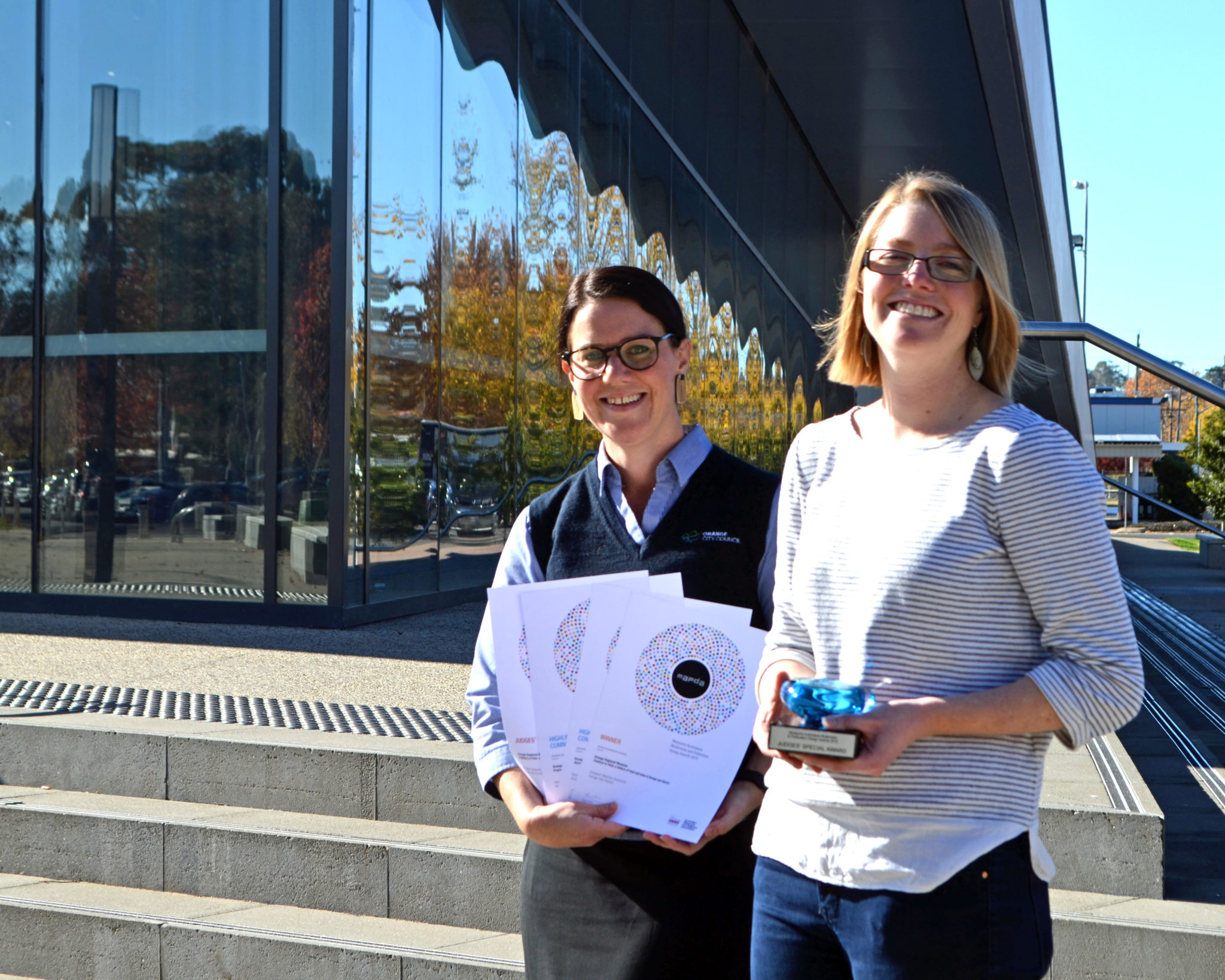 Graphic designer Natasha Townsend and museum manager Allison Campbell with a suite of awards from the Museums Australasia Publication Design Awards