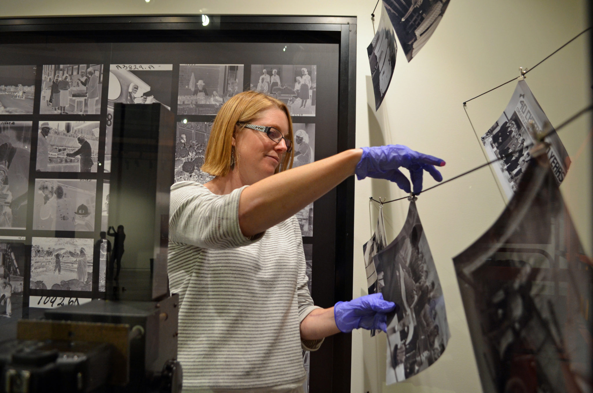 Woman placing photos on display