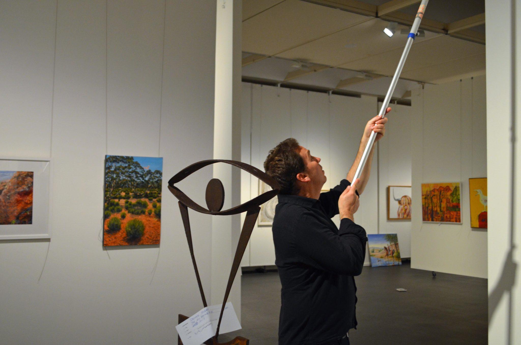 Gallery director Brad Hammond installs last year's Here Now exhibition