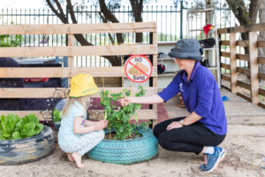 Child planting herbs with an educator