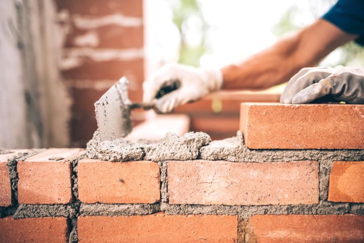 Brick layer building a wall