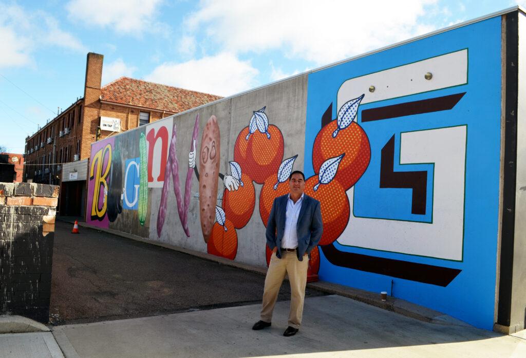 Cr Tony Mileto inspects the new mural in McNamara Street