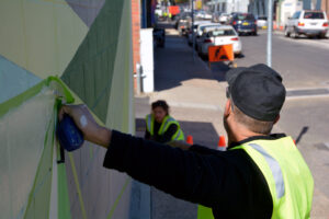 Artist Yanni Pounartzis working on his piece in McNamara Street